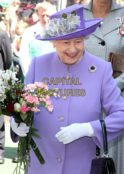 Her Majesty Queen Elizabeth II continues her Diamond Jubilee tour of Britain with a visit to the Hertfordshire market town of Hitchin, England..June 14th 2012.HRH royal royalty half length purple coat hat white gloves flowers bouquet smiling .CAP/JIL.©Jill Mayhew/Capital Pictures