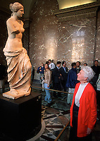 A senior female tourist smiles as she views the Venus De Milo statue in the interior of the Louvre Museum. Paris, France.