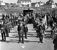 The Killarney Brass and Reed Band leading the 1973 St Patrick's Day parade through the town. Left hand side, front to back, Mossie Kelly, John Carroll, Mick Horgan, Mike Murphy, Pat Shortt, Timmy Corkery and Joe Campbell. Centre, front to back, Tim O'Meara, John O'Mahony, Jim Doyle, Tim Bartlett, Paddy O'Mahony and Tom Murphy. Right hand side from front to back, Johnny Foran, Danno Foran, Geoff O'Donoghue, Barney Moloney (partly hidden), Harry Bartlett, DJ Fleming and Tim Lynch. The tri-colour bearer to the right of picture is Christy ODonoghue/<br />
