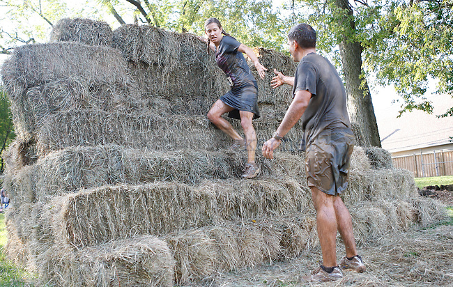 Participants climb down hay bales at the Mud Run near Commonwealth Stadium in Lexington, Ky., on Saturday, September 22, 2012. Photo by Tessa Lighty | Staff