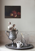 Still life of cutlery stored in a pewter goblet in the kitchen. A painting of peaches on the wall behind gives the whole a distinctly 17th century French feel