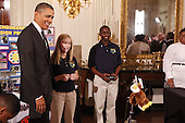 United States President Barack Obama watches a robot with students Morgan Ard (C) and Titus Walker, 8th grade students at Monroeville Jr. High School in Monroeville, Alabama who won high honors at the South BEST robotics competition, while touring student science fair projects on exhibt at the White House in Washington, D.C. on February 7, 2012.  Obama hosted the second White House Science Fair celebrating the student winners of science, technology, engineering and math (STEM) competitions from across the country. .Credit: Molly Riley / Pool via CNP