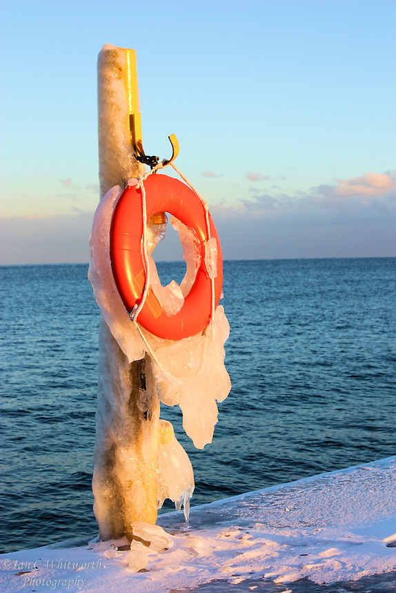 A wintery view of a life preserver on the lighthouse pier in Oakville, Ontario