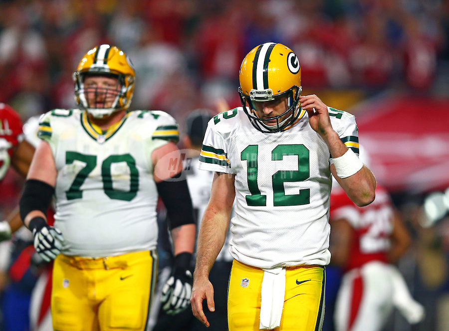 Dec 27, 2015; Glendale, AZ, USA; Green Bay Packers quarterback Aaron Rodgers (12) reacts alongside offensive guard T.J. Lang (70) against the Arizona Cardinals at University of Phoenix Stadium. The Cardinals defeated the Packers 38-8. Mandatory Credit: Mark J. Rebilas-USA TODAY Sports