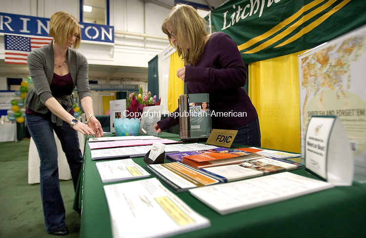 TORRINGTON CT. 04 April 2014-040414SV06-From left, Melissa Root and Barbara Bartholomew of  Litchfield Bancorp set up their booth at the Northwest Connecticut Chamber of Commerce Northwest Expo at the Armory in Torrington Friday. <br /> Steven Valenti Republican-American