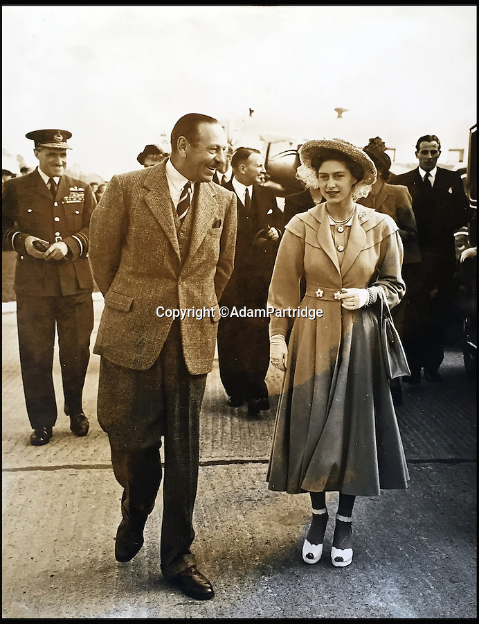 BNPS.co.uk (01202 558833)<br /> Pic: AdamPartridge/BNPS<br /> <br /> Alexander Usher pictured on the right in the background.<br /> <br /> A fascinating photo archive that documents the dedication of one of the Queen's bodyguards has come to light 70 years later.<br /> <br /> Police Inspector Alexander Usher was appointed 'No.1 Shadow' to Princess Elizabeth in 1944, when she was aged 18 and 'heir presumptive' to the throne behind her father King George VI.<br /> <br /> Mr Usher served alongside her until 1951, by which time she had married Prince Philip. He even went on their honeymoon.<br /> <br /> The album of photo which he features in is now being sold by Adam Partridge auctioneers.