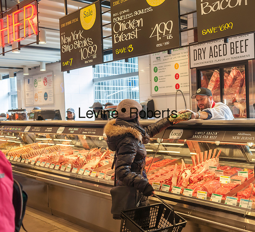 A shopper chooses cuts of meat in the new Whole Foods Market opposite Bryant Park in New York on opening day Saturday, January 28, 2017. The store in Midtown Manhattan is the chain's 11th store to open in the city. The store has a large selection of prepared foods from a diverse group of vendors inside the store.  (© Richard B. Levine)