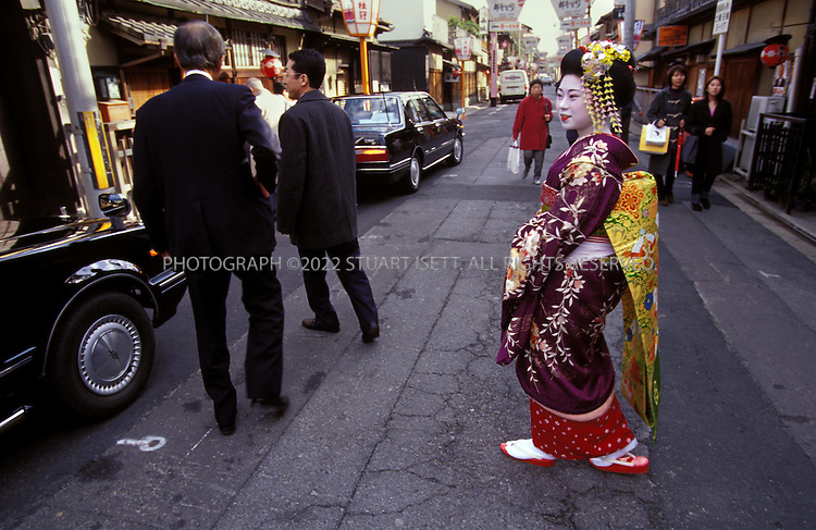 Kyoto, Japan..A young geisha sends off customers from one of the Gion's exclusive tea houses...All photographs ©2003 Stuart Isett.All rights reserved.
