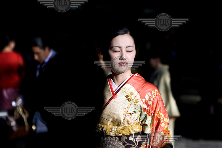 A woman, dressed in an ornate Kimono, closes her eyes in the bright sunshine while she attends a Shinto wedding at the Meiji Jingu Shinto Shrine. /Felix Features