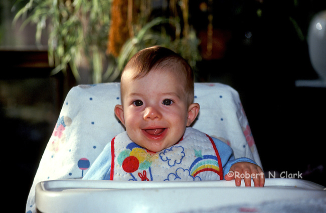 Boy in high chair smiling and laughing