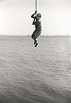 John swinging on rope over Lake Skaneateles. File#73-145-D25