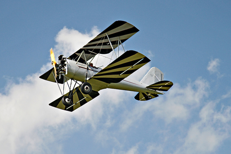 A silver-bodied, Meyers OTW (out-to-win) bi-plane with black and white striped wings flies in a beautiful blue, cloud-filled, sky at the 2010 Wings 'n' Wheels Showcase. The white stripe on the wings takes on a yellow shade in the sun.
