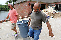 NWA Democrat-Gazette/DAVID GOTTSCHALK Jeff Fenwick (left) helps Walid Mady carry debris from his home Tuesday, June 4, 2019, to a dumpster on Turtle Bay Drive in Fort Smith. Homes in the neighborhood are beginning the process of recovering following flooding by the Arkansas River.