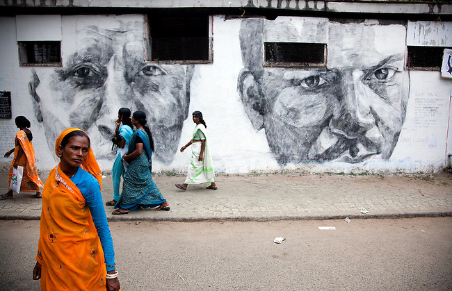 16 December, 2012, Kochin, INDIA: Local women walk past giant charcoal murals of Australian artist Daniel Connell on the streets of Fort Kochi at the Kochi-Muziris Biennale. Aussie artists on display at  India's first Biennale in Kerala. The Biennale curators travelled Down Under to select an exciting group of artists to take part in this celebration of contemporary art from around the world, which is expected to become one of Asia's best arts events. The Biennale  acknowledges the cosmopolitan modernity of Kochi and the international connections established by the ancient port of Muziris that existed 30km north of Kerala's current commercial capital. Picture by Graham Crouch/DFAT