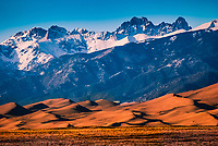 The 14,000 foot high Crestone Group towers above the wind swept Great Sand Dunes below.