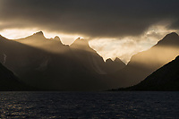 Dramatic light shines over mountains during clearing summer storm, Reine, Moskenesøy, Lofoten Islands, Norway