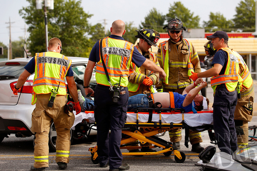 NWA Media/JASON IVESTER --08/22/2014--<br /> Rogers Fire Department members tend to a victim following a three-vehicle accident on Friday, Aug. 22, 2014, at the intersection of 13th Street and Walnut Street in Rogers. Only one person involved in the accident was transported with injuries from the accident. Rogers Fire had to extricate the individual from the vehicle.
