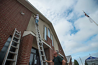 NWA Democrat-Gazette/ANTHONY REYES • @NWATONYR<br /> David Mabry, bottom, holds the ladder steady for Mike Brown, both with David Mabry Building Inc. of Lowell, as he paints the stucco Wednesday, Sept. 9, 2015 on the front of the First Baptist Church in Lowell. The pair have been working on remodels inside and outside the church for a few weeks.