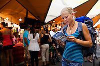 A young backpacker reads her guidebook in front of the markets at The Rocks district.  Sydney, New South Wales, AUSTRALIA