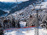 Switzerland. Canton Valais. Cable car above Verbier and skiiers on slope. Verbier is a village located in the municipality of Bagnes. The village lies on a south orientated terrace at around 1,500 metres facing the Grand Combin massif. The terrace lies on the east side of the Val de Bagnes. Verbier had 3000 permanent residents in 2010. The number of residents can rise to 35,000 in the winter season. Verbier is one of the largest holiday resort and ski areas in the Swiss Alps. 3.01.2012 © 2012 Didier Ruef