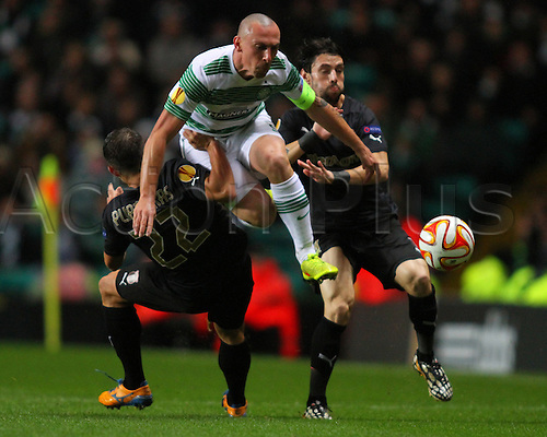 23.10.2014.  Glasgow, Scotland. UEFA Europa League. Celtic versus Astra Giurgiu. Scott Brown hurdles Vassilis Pliatsikas tackle