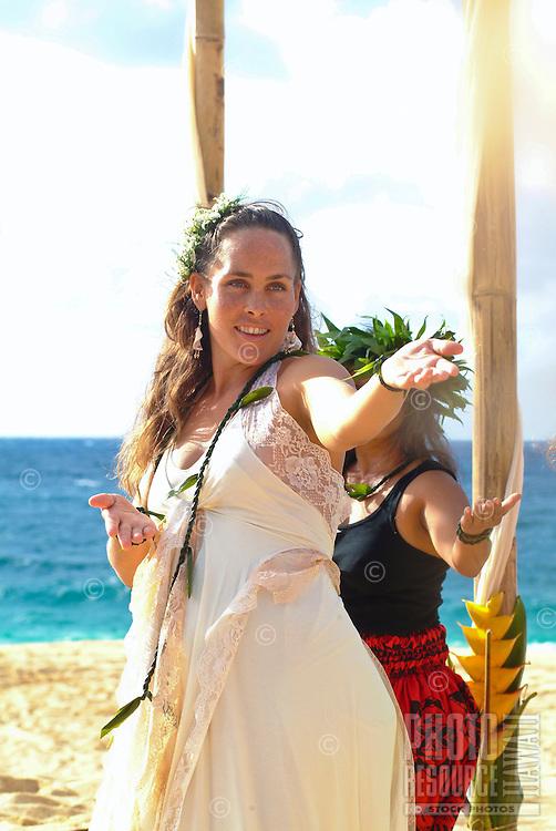 Young local bride performing hula at her wedding on Ke'iki Beach, North Shore