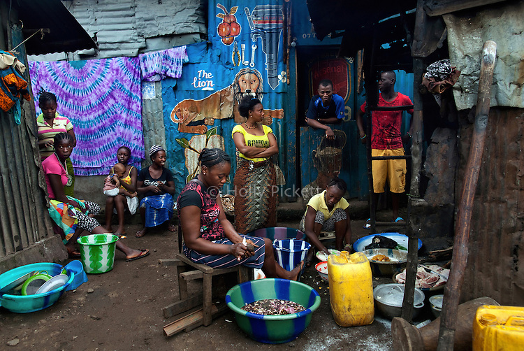 Sitting outside her home, Mariatu Kamara, center, peels potatoes for stew to sell in the market in Mabella quarter, Freetown, Sierra Leone, Aug. 15, 2012. Many residents of the impoverished quarter lack access to basic sanitation or drinkable water. Médecins Sans Frontières Belgium, in collaboration with the Sierra Leone Ministry of Health, is running four emergency cholera treatment centers to keep up with the number of patients. Many of the roughly 120 daily patients seen by the MSF team come from extremely impoverished areas of the densely-populated capital, where proper systems for drainage and waste disposal are almost non-existent. Outbreaks of water-borne diseases like cholera become even more likely during the rainy season, which is expected to last at least two more months.