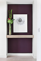 An elegant flower arrangement is placed on a light wood shelf set in a recess with a purple painted background.