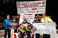 Pete Kaiser sits with his lead dogs Marrow (L) and Lucy and the principal sponsors at the Nome finish line after winning the 2019 Iditarod Trail Sled Dog Race. Pete's winning time is 9 days 12 hours 39 minutes and 6 seconds<br /> <br /> Photo by Jeff Schultz/  (C) 2019  ALL RIGHTS RESERVED