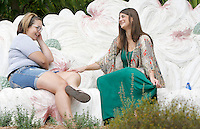 NWA Democrat-Gazette/DAVID GOTTSCHALK  Friends Haley Marshall (left) and Nicole Silvey spend time talking Friday, August 28, 2015 in Wilson Park in Fayetteville. The two were sitting on the 12-foot long dogwood blossom bench designed and built by Eugene Sargent.