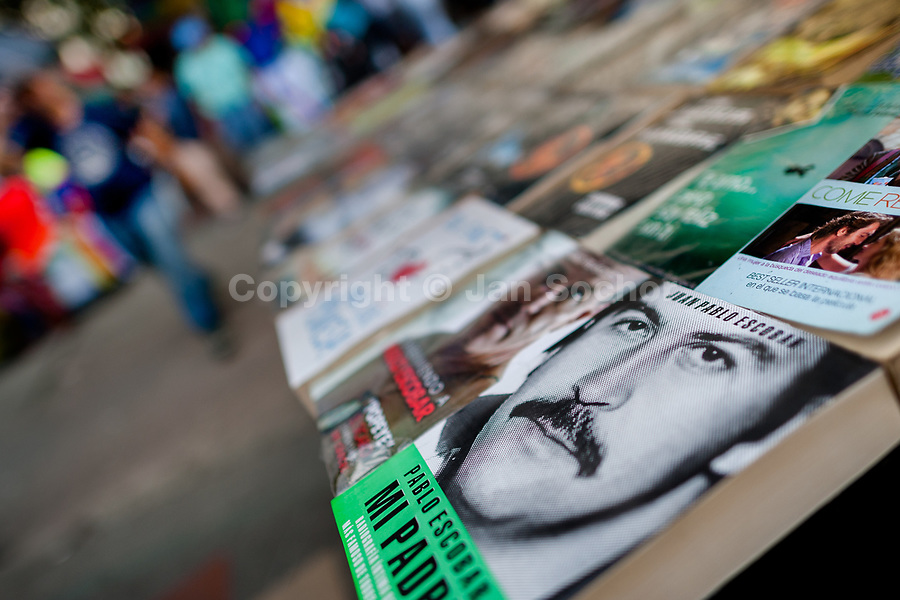 "A paperback book, depicting the drug lord Pablo Escobar on the cover, is seen arranged at the market stand on the street in Medellín, Colombia, 7 December 2017. Twenty five years after Pablo Escobar's death, the legacy of the Medellín Cartel leader is alive and flourishing. Although many Colombians who lived through the decades of drug wars, assassinations, kidnappings, reject Pablo Escobar's cult and his celebrity status, there is a significant number of Colombians who admire him, worshipping the questionable ""Robin Hood"" image he had. Moreover, in the recent years, the popular ""Narcos"" TV series has inspired thousands of tourists to visit Medellín, creating a booming business for many but causing a controversial rise of narco-tourism."