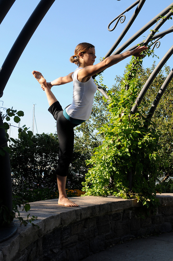 A beautiful young woman practicing yoga at Toronto Music Gardens