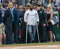 David Bailey, one of the US Capitol Hil police, who was wounded in  a shooting at a practice baseball game in Virginia, yesterday, watches the teams warm up. Since 1909, Democratic and Republican Member of the House and Senate have held an annual baseball game.  This year, due to shooting of House Majority Whip, Steve Scalise, R-LA, the teams showed their unity by wearing Capitol Hill Police ball caps to honor the officers that were wounded protecting Scalise and other Members of Congress. Patsy Lynch/MediaPunch