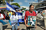 Priscila Cartagena (right) holds a photo of her daughter Yesenia Marleni Gaitán Cartagena as she walks with a group of Central Americans during a demonstration in the center of Tapachula, Mexico, on December 16, 2013. The group, mostly mothers looking for their children, spent 17 days touring 14 Mexican states in search of their loved ones, most of whom had disappeared while following the migrant trail north. <br /> <br /> Cartagena, who lives in Tegucigalpa, says her daughter migrated north in 2008, headed to the United States, and last called her from Nuevo Laredo, Mexico. She hasn't heard from her since.