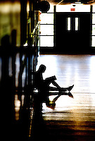 Stock photo / illustration of a student sitting in hallway, leaning against lockers, silhouetted. Photo taken at Myers Park High School in Charlotte, NC.
