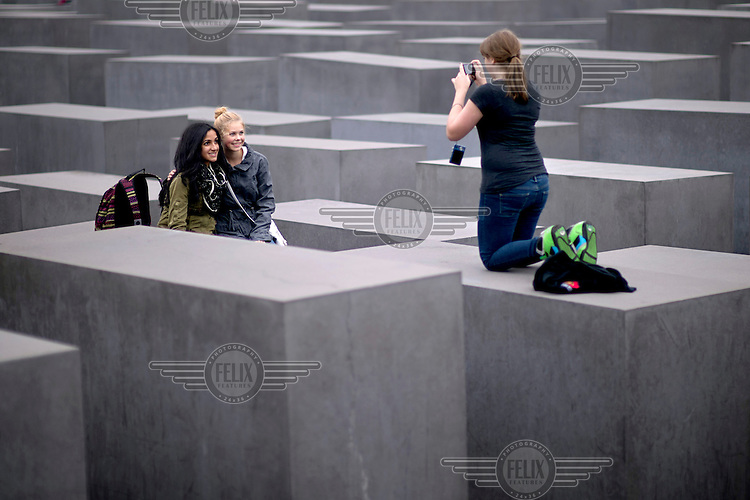 A group of young women take each others photographs among the stelae that form the Holocaust Memorial.