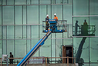 Two unidentified workers put finishing touches on the new Lambton College Athletics & Fitness Complex scheduled to officially open in October