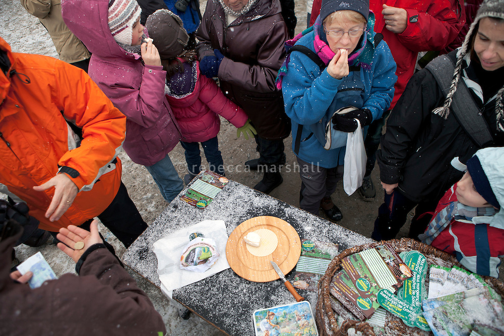 Market-goers sample reblochon cheese at a tasting organised by local reblochon producers at the weekly Wednesday morning market, Le Grand Bornand, France, 15 February 2012.