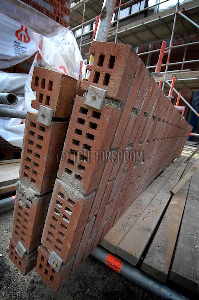 AMSTERDAM - In Amsterdam-Osdorp heeft uitvoerder Ben Brandjes van Thunnissen Bouw prefab metselwerk ontwikkeld op basis van het rijgen van gaatjesstenen aan draadstangen. In overleg met metselbedrijf de Noord uit Waarland werden naast de keet frames geplaatst waar de metselaars penanten konden metselen tot een maximum hoogte van 3,5 meter, die na week uitharden met hulp van een door staalconstructiebedrijf Jack Zoon uit Heiloo ontwikkelde kantelconstructie tegen de gevels werden geplaatst en vastgezet. Op de manier lukte het na berekeningen door werkvoorbereider Bart Doeven om 14 verschillende lengtes te bouwen met 3 verschillende steensoorten. Op deze opmerkelijke en efficiënte wijze verwerkt Thunnissen Bouw in totaal 28.000 stenen, die resulteren in strakke beeldbepalende metselgevels. COPYRIGHT TON BORSBOOM..