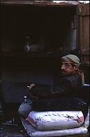 Yemen Sana'a, tradesman sitting and chewing qat,  a plant that contains the alkaloid cathinone, a stimulant, which is said to cause excitement