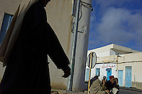Near the Libyan border men gather on the streets talking