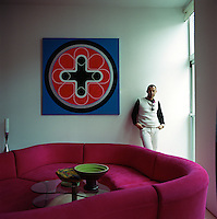 Portrait of interior designer Karim Rashid standing in his living room behind a bright pink sofa