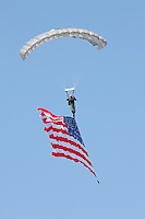 The stars and stripes makes its way down to earth beneath the canopy of a parachutists during the 2008 Reno National Championship Air Races.