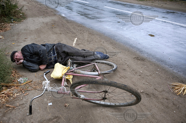 A drunk man lies on the roadside after falling off his bicycle.