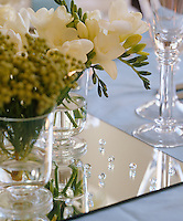 Fragrant cut freesias adorn a mirror table setting on a dining table