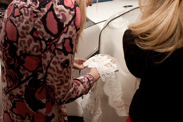 November 27, 2012. Charleston, South Carolina.. Alexa Wyatt and bride of the weekend, Elise Griswold (soon to be Nuckols), look at the lace on the wedding dress.. Alexa Wyatt, 23, is an Event Coordinator with Southern Protocol, a boutique wedding and event planning company in Charleston, SC..