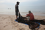 Fishermen sort through the morning's catch on the beach in Mui Ne, Vietnam. Nov. 20, 2011.