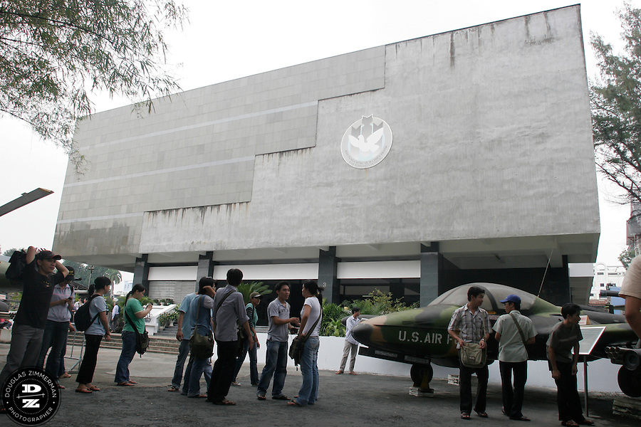 Visitors outside the War Remnants Museum in Ho Chi Minh City, Vietnam.  The museum documents the atrocities committed by the American military while fighting in Vietnam.  It also houses many US armored vehicles and aircrafts used during the Vietnam War. Photograph by Douglas ZImmerman