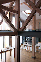 Dramatic contemporary roof beams criss-cross the double-height kitchen area which is furnished with white lacquer units and a grey-painted wooden dresser