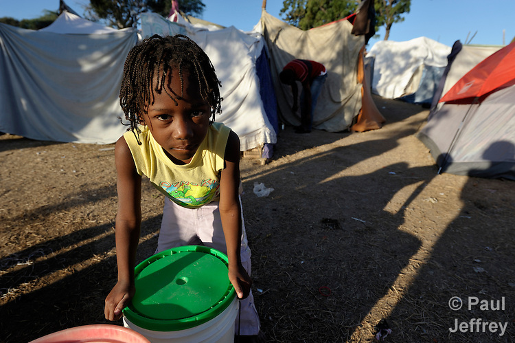 A girl rests after carrying water uphill in a camp for homeless families set up on a golf course in Port-au-Prince, Haiti, which was ravaged by a January 12 earthquake.
